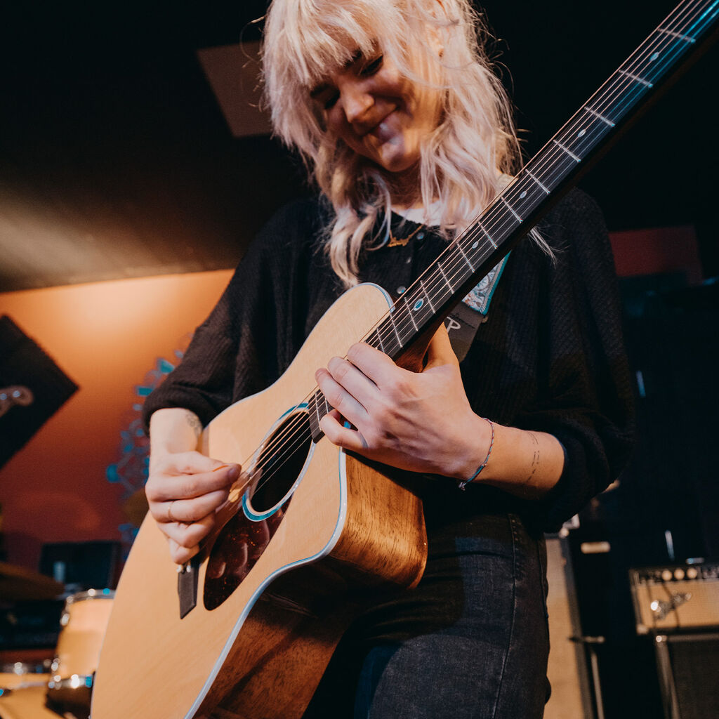 Girl playing acoustic electric guitar